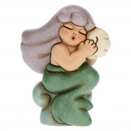 Magic mermaid holding a shell to her ear